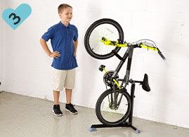Boy has successfully placed his bike upright in the Bike Nook