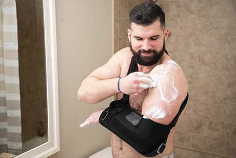 man with arm brace cleaning