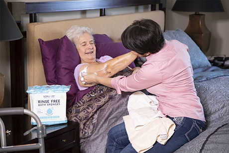 cleaning elderly woman in bed