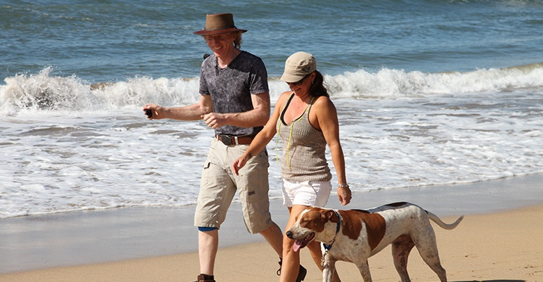 Don walking with Woman and her dog on a beach