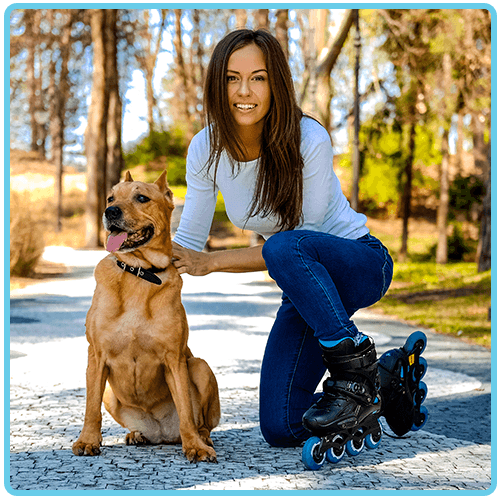 Rollerblader kneeling with her dog